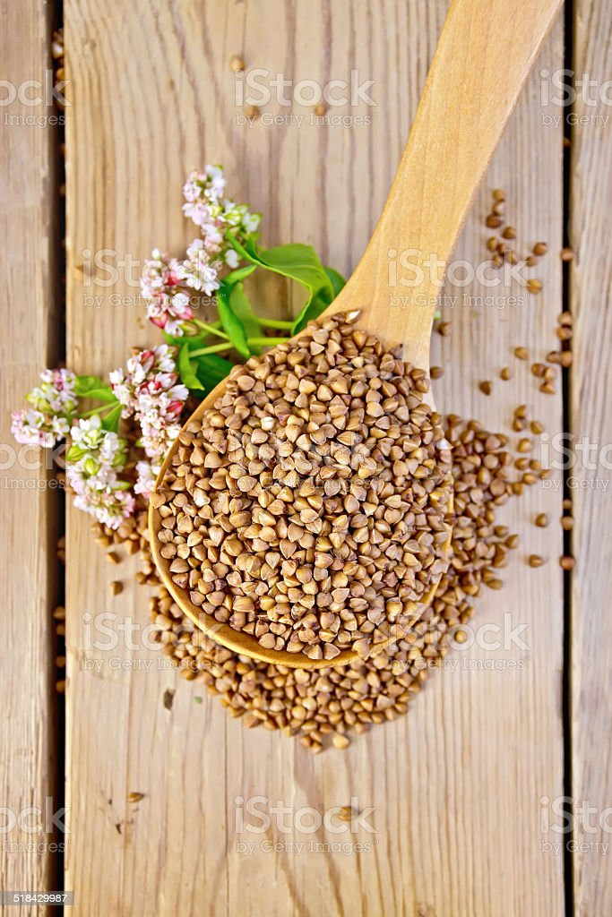 Buckwheat in spoon with flower on board stock photo