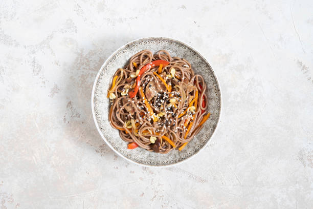 boekweit noedels met groenten en vlees versierd met sesam in kom op grijze achtergrond. - sobanoedels stockfoto's en -beelden