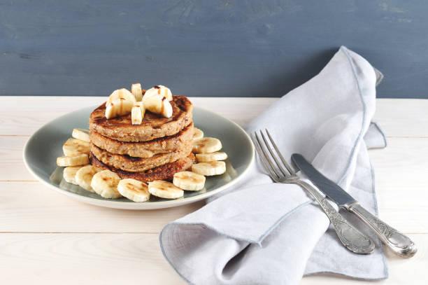 buchweizenpfannkuchen werden auf die andere gelegt. pfannkuchen werden mit bananenscheiben verziert und mit schokoladensirup gegossen. - buchweizenpfannkuchen stock-fotos und bilder