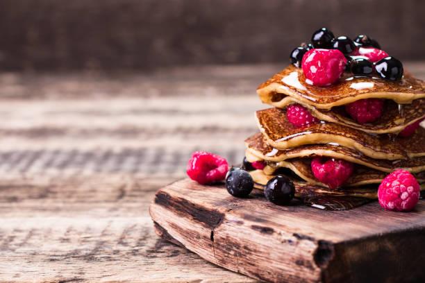 buchweizen pfannkuchen mit beeren-früchten und honig auf vintage holztisch - buchweizenpfannkuchen stock-fotos und bilder