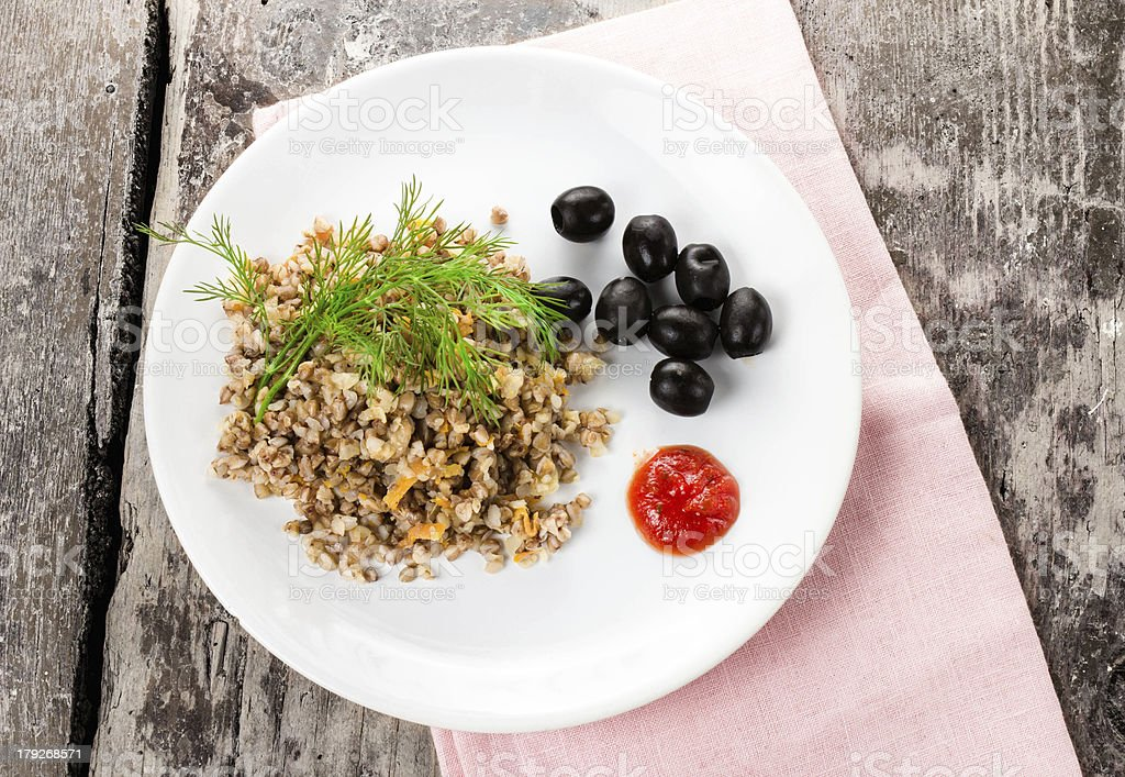 Buckwheat porridge, black olives and herbs royalty-free stock photo