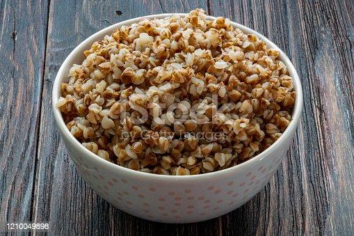 Buckwheat porridge in a ceramic bowl on a wooden table