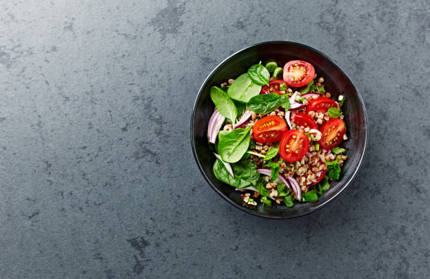 Buckwheat salad with cherry tomatoes and baby spinach stock photo