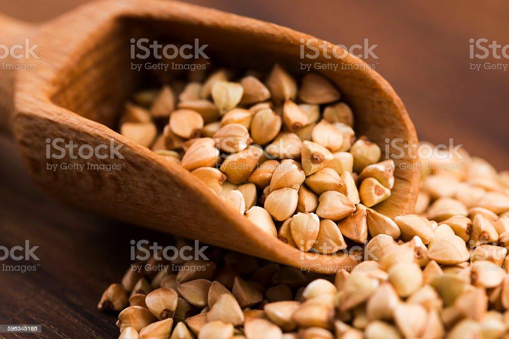 Buckwheat with a spoon on a wooden boards background Lizenzfreies stock-foto
