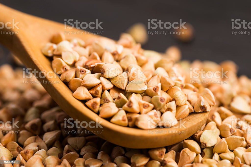 Buckwheat with a spoon on a wooden boards background royalty-free stock photo