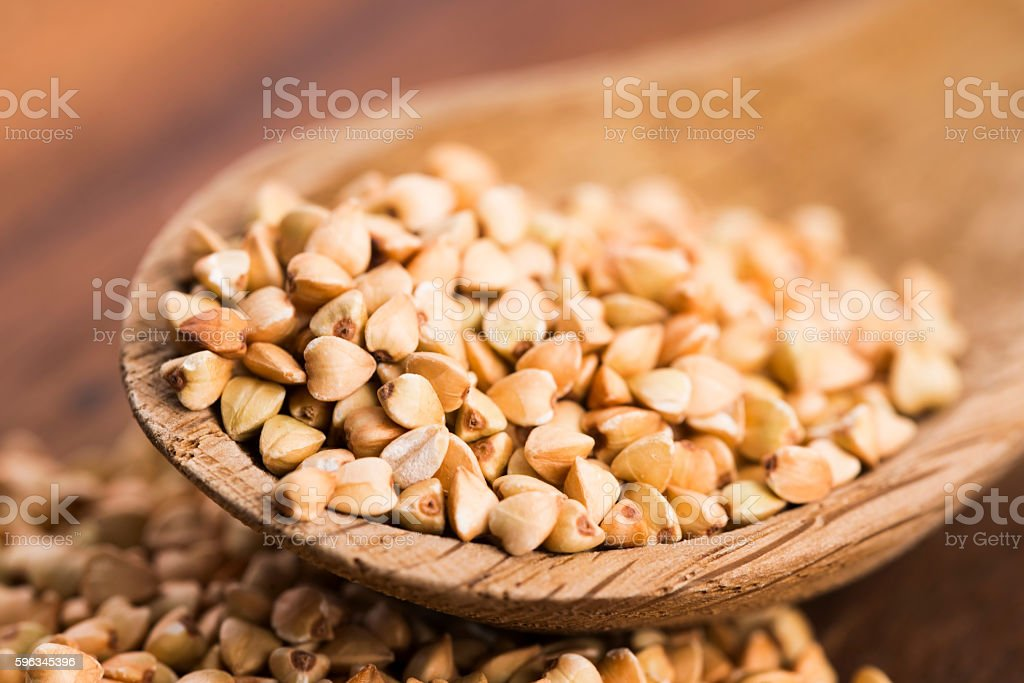 Buckwheat with a spoon on a wooden boards background Lizenzfreies stock-foto