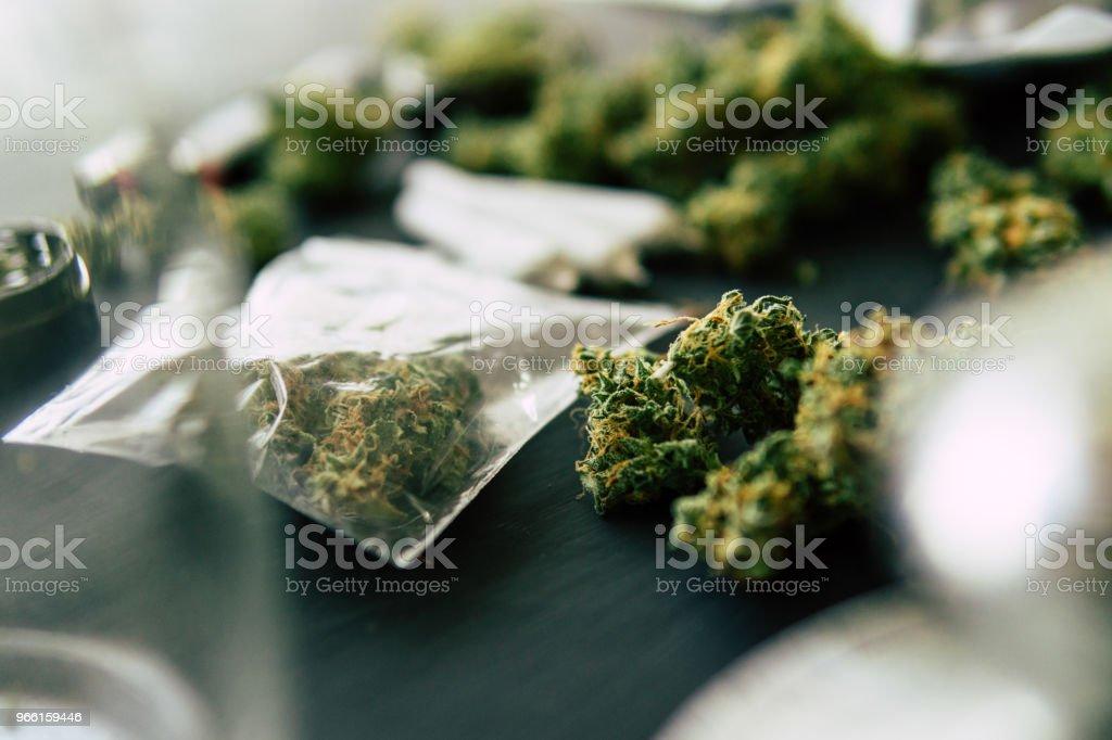 yema brote de marihuana en escalas, amoladora y cannabis rallado común y un paquete de hierbas y Smartphone en un fondo de madera negro cerrar - Foto de stock de Agricultura libre de derechos
