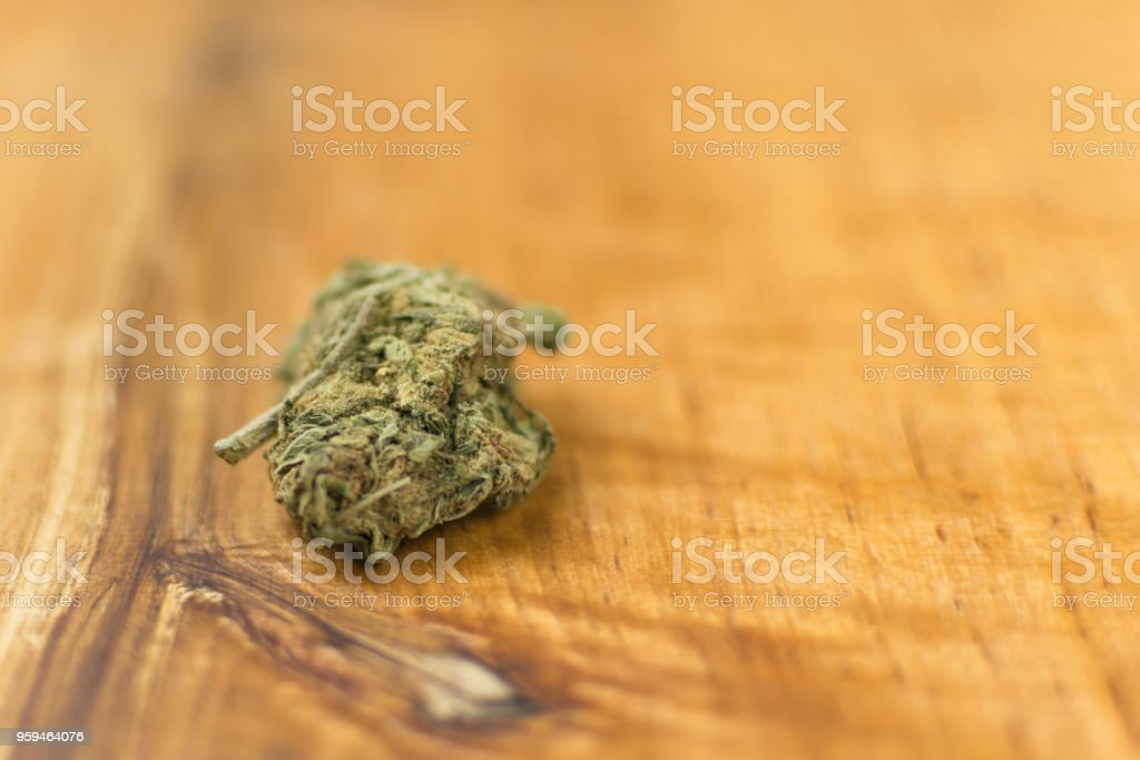 A bud of marijuana on a wooden background. stock photo