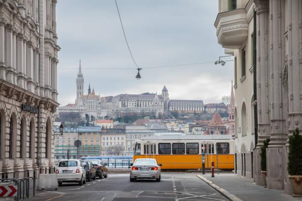 路面電車と車の前面に渡すと害虫から見たブダ城。 城は歴史的な宮殿はハンガリーの王の複雑な - マーチャーシュ教会 ストックフォトと画像