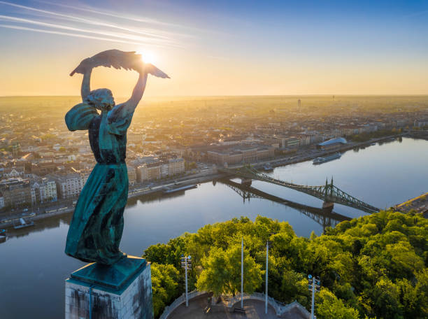 Budapest, Hungary - Aerial view from the top of Gellert Hill with Statue of Liberty, Liberty Bridge and skyline of Budapest at sunrise stock photo