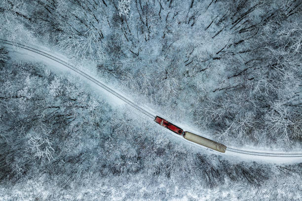 Budapest, Hungary - Aerial view of snowy forest with red train on a track at winter time, captured from above stock photo