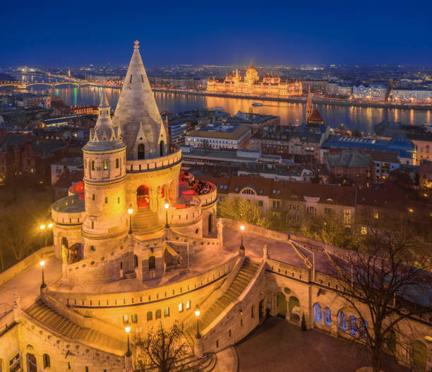 Budapest, Hungary - Aerial view of the main tower of Fisherman's Bastion (Halaszbastya) with illuminated Parliament of Hungary stock photo