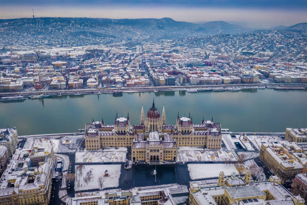 Budapest, Hungary - Aerial view of the snowy Parliament of Hungary at winter time with River Danube and Fisherman's Bastion stock photo