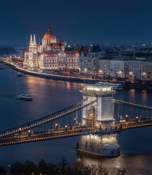Budapest, Hungary - Beautiful illuminated Szechenyi Chain Bridge with the Parliament of Hungary at blue hour with sightseeing boat stock photo