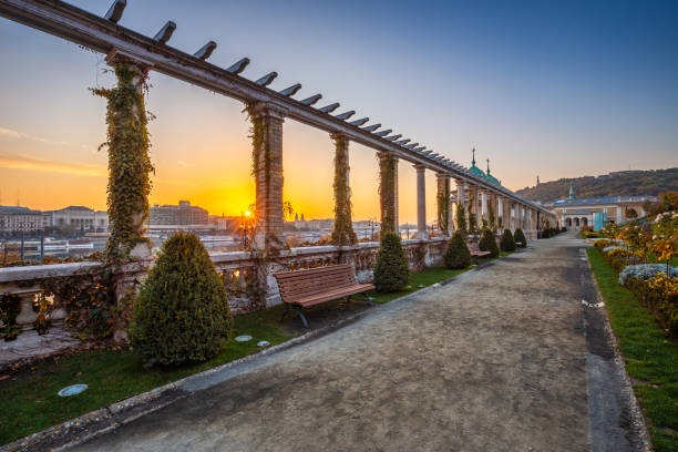 Budapest, Hungary - Beautiful sunrise at Varkert Bazaar with bench, Statue of Liberty at background stock photo