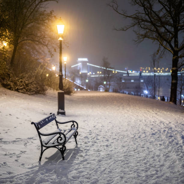Budapest, Hungary - Bench and lamp post in a snowy park at Buda district with Szechenyi Chain Bridge at background during heavy snowing at winter time stock photo