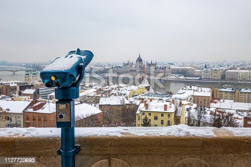 istock Budapest, Hungary - Blue binoculars with the view of Pest with Parliament building on a cold winter day 1127720693