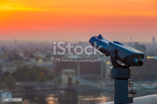 istock Budapest, Hungary - Blue binoculars with the view of Pest with Szechenyi Chain Bridge and beautiful golden sky 1067743260