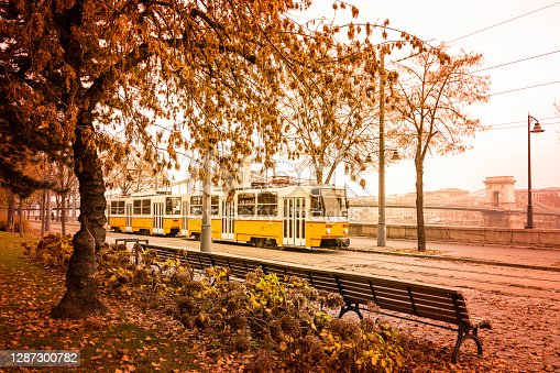 An old tram passing by the lonely bench at the Danube riverbank near the Chain Bridge in late autumn.