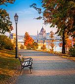 Budapest, Hungary - Romantic sunrise scene at Buda district with bench, lamp post, autumn foliage, Szechenyi Chain Bridge and Parliament at background