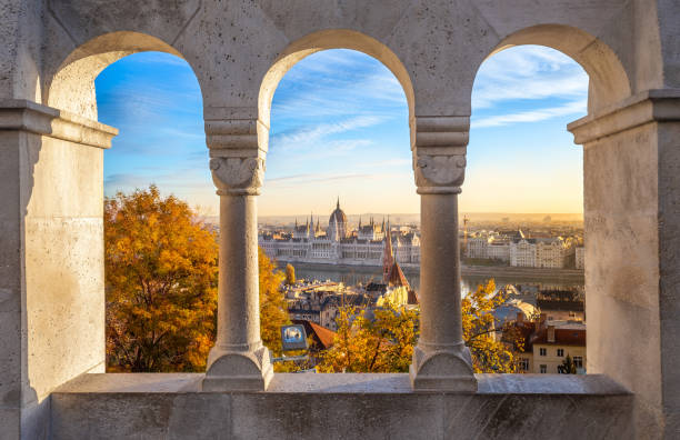 Budapest, Hungary - The beautiful Hungarian Parliament building through old windows of Buda District at sunrise stock photo