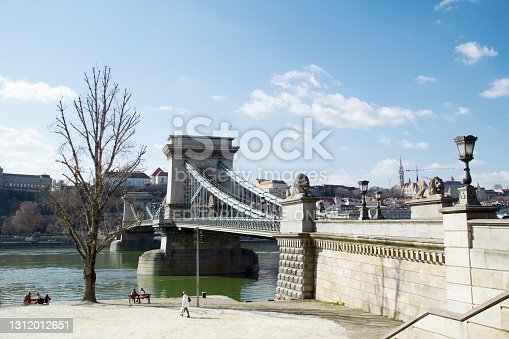 People Relaxing in Pedestrian Zone of Danube Riverbank by Széchenyi Chain Bridge with Blue Sky in Budapest, Hungary in March 2021 - The Széchenyi Chain Bridge is a chain bridge that spans the River Danube between Buda and Pest, the western and eastern sides of Budapest, the capital of Hungary. It was opened in 1849.