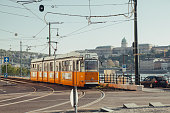 Budapest,Hungary - April 21,2017 : A Budapest yellow tram riding alongside the Danube River. The Yellow tram is the traditional Budapest transportation way for locals and tourists.