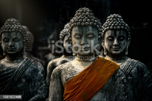 Buddah statue with ancient stupas with orange cloth in Buddhist temple on black background at saraburi, thailand