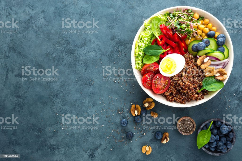 Buddha bowl dinner with boiled egg, chickpea, fresh tomato, sweet pepper, cucumber, savoy cabbage, red onion, green sprouts, spinach leaves, blueberry, walnuts, chia and quinoa. Healthy dish, lunch bowl. Detox diet. Balanced food. Top view stock photo