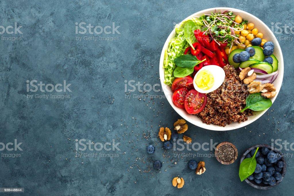 Dîner de bol Bouddha avec œuf à la coque, pois chiches, tomates fraîches, poivron, concombre, chou frisé, oignon rouge, vert choux, épinards, myrtille, noix, clerbois et quinoa. Plat sain, bol déjeuner. Régime de désintoxication. Alimentation équilibrée. Vue de dessus - Photo