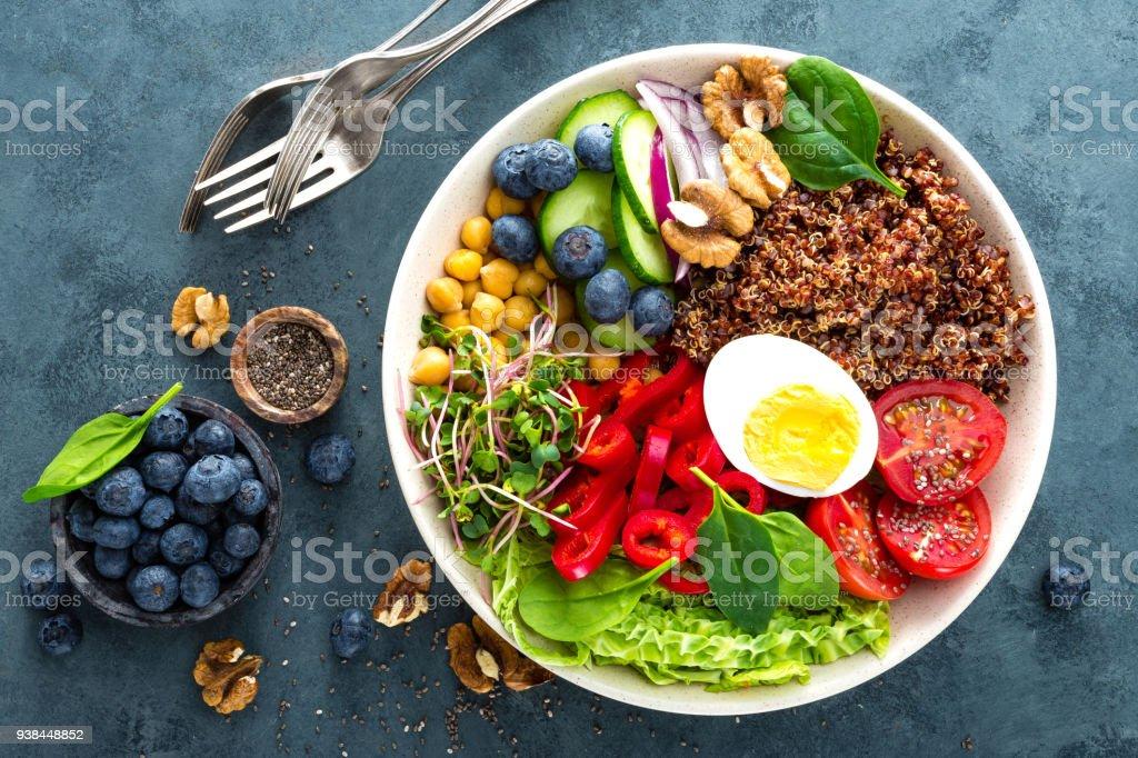 Dîner de bol Bouddha avec œuf à la coque, pois chiches, tomates fraîches, poivron, concombre, chou frisé, oignon rouge, vert choux, épinards, myrtille, noix, clerbois et quinoa. Plat sain, bol déjeuner. Régime de désintoxication. Alimentation équilibrée. Vue de dessus photo libre de droits