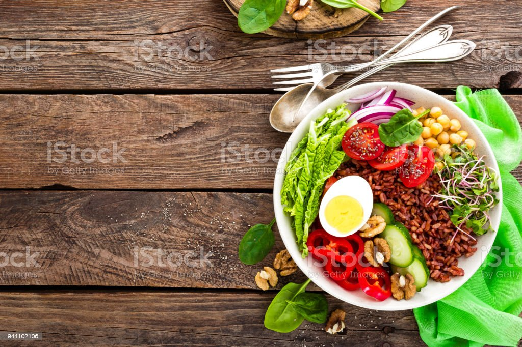 Buddha bowl dish with boiled egg, chickpea, fresh tomato, sweet pepper, cucumber, savoy cabbage, red onion, green sprouts, spinach leaves, walnuts, chia and rice stock photo