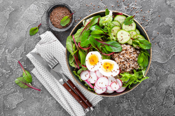 Buddha bowl dish with buckwheat porridge, boiled egg, fresh vegetable salad of radish, cucumber, lettuce and chard leaves. Healthy lunch menu. Top view stock photo