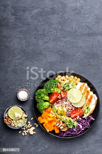 istock Buddha bowl dish with chicken fillet, brown rice, avocado, pepper, tomato, broccoli, red cabbage, chickpea, fresh lettuce salad, pine nuts and walnuts. Healthy balanced eating. Top view with space for a text 934408372