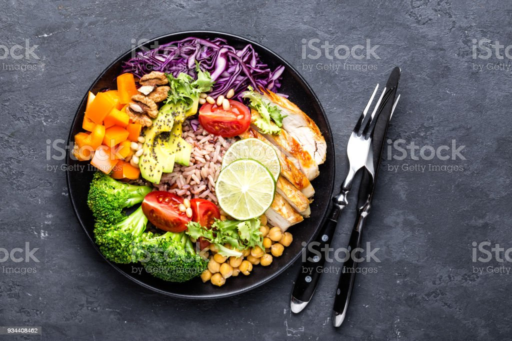 Buddha bowl dish with chicken fillet, brown rice, avocado, pepper, tomato, broccoli, red cabbage, chickpea, fresh lettuce salad, pine nuts and walnuts. Healthy balanced eating. Top view stock photo
