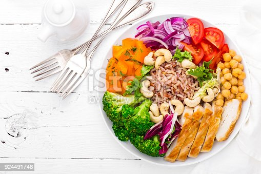 istock Buddha bowl dish with chicken fillet, brown rice, pepper, tomato, broccoli, onion, chickpea, fresh lettuce salad, cashew and walnuts. Healthy balanced eating. Top view. White background 924491746
