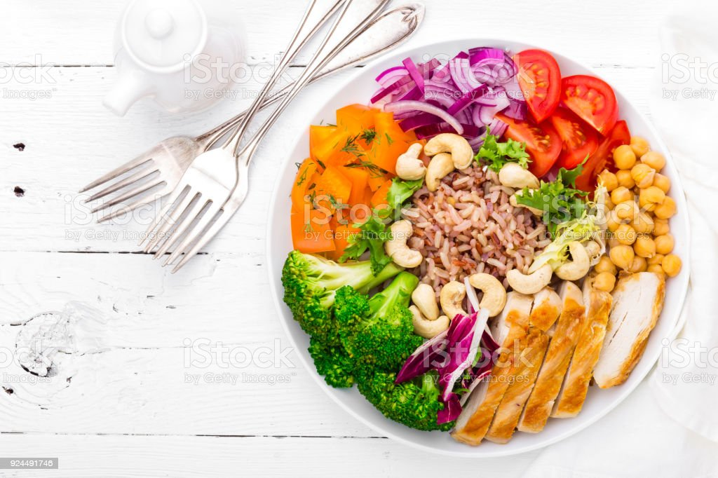 Buddha bowl dish with chicken fillet, brown rice, pepper, tomato, broccoli, onion, chickpea, fresh lettuce salad, cashew and walnuts. Healthy balanced eating. Top view. White background stock photo