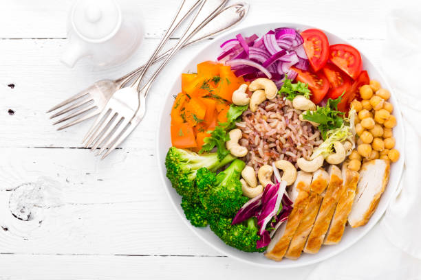 buddha bowl dish with chicken fillet, brown rice, pepper, tomato, broccoli, onion, chickpea, fresh lettuce salad, cashew and walnuts. healthy balanced eating. top view. white background - mangiare sano foto e immagini stock