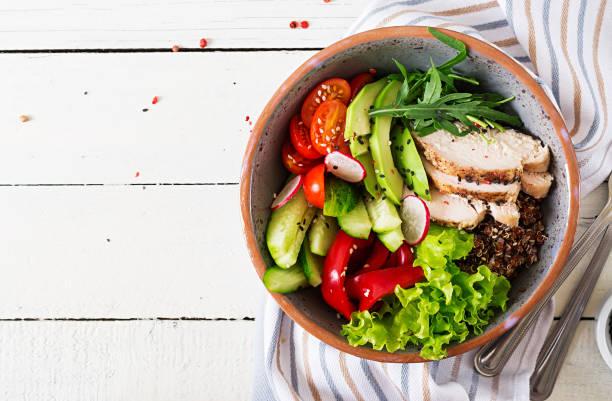 buddha schüssel schüssel mit hähnchenfilet, quinoa, avocado, paprika, tomaten, gurken, radieschen, frischem blattsalat und sesam. detox und gesunde superfoods schüssel konzept. overhead, top aussicht, flach zu legen. - quinoa superfood stock-fotos und bilder