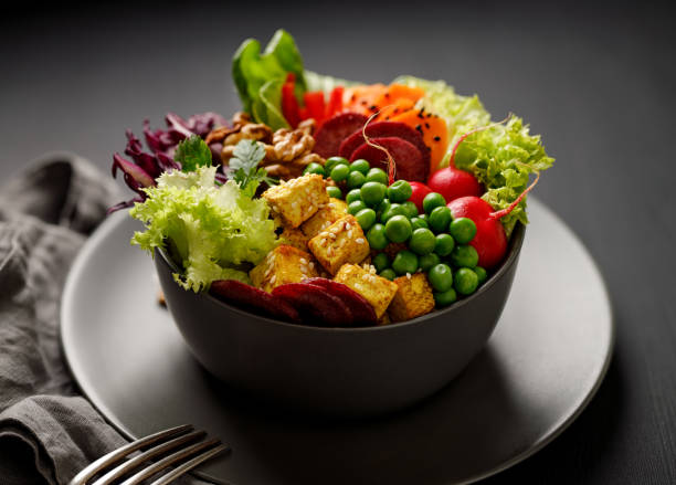 Buddha bowl,  healthy and nutritious salad with a variety of vegetables, nuts and tofu cheese stock photo
