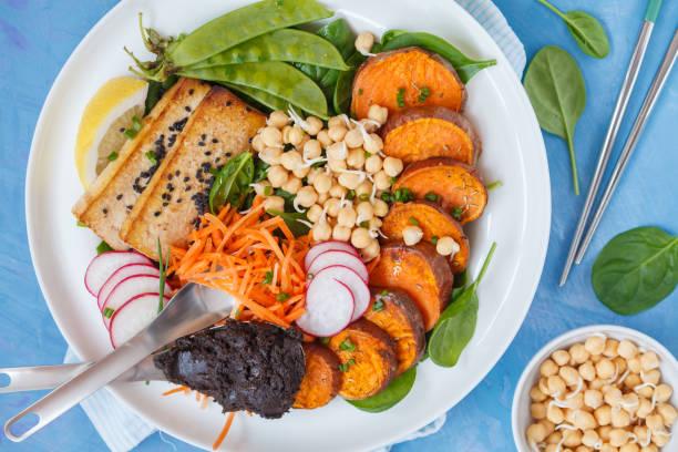 buddha vegan salatschüssel mit gemüse, tofu, gebackene süßkartoffel, sprossen, kichererbsen und hanf dressing. - englischer erbsen salat stock-fotos und bilder