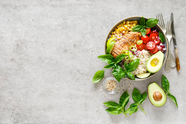 Buddha bowl with grilled chicken breast, tomato, onion, corn, avocado, fresh basil salad and rice, healthy balanced eating for lunch stock photo