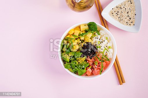 istock Buddha bowl with rice, mango, avocado and salmon. Healthy food concept. Top view. Flat lay 1142404701