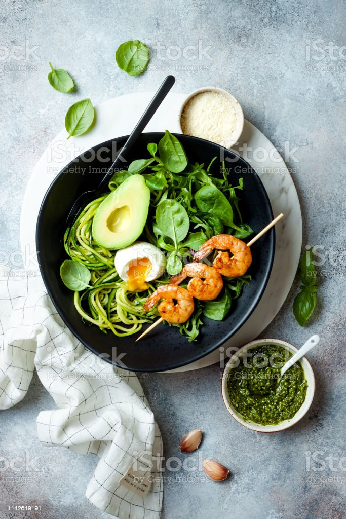 Buddha bowl with soft boiled egg, avocado, greens, zucchini noodles, grilled shrimps and pesto sauce. Vegetarian vegetable low carb lunch bowl. royalty-free stock photo