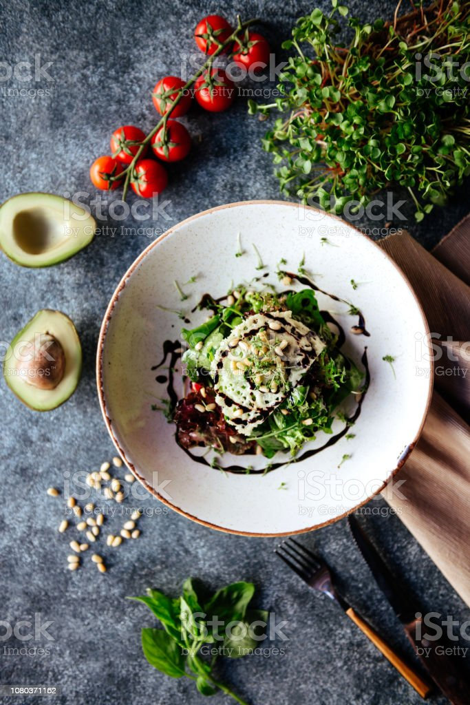 Buddha bowl with spinach salad, quinoa, roasted chickpeas, grilled chicken, avocado, tomatoes, cucumbers, sesame seeds. stock photo
