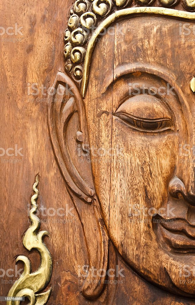 Buddha' face, carving from teak wood in Thai style royalty-free stock photo