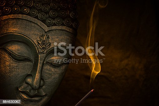 Buddha face with incense stick