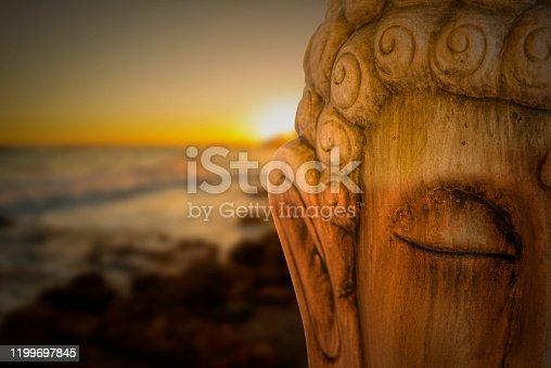 Buddha figure meditating with a sunrise on the beach, Spain