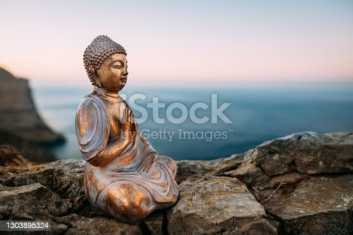 istock Buddha figure sitting on a rock in front of mountains and the mediterranean sea on Majorca during the sunset 1303895324