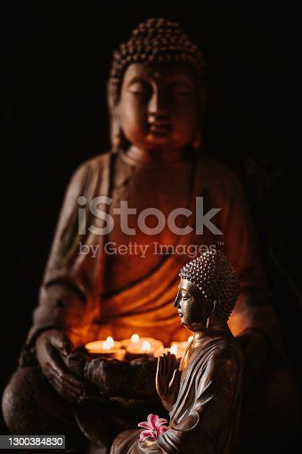 istock Buddha figurine seen in profile with a flower in front of another buddha holding lit candles in the hands 1300384830